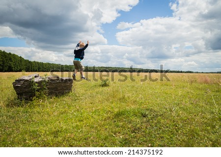 Little boy in the middle of the field on the stone. Kid jumping from stone. Boy, nature, jump, rock, freedom, childhood - Concept of carefree childhood. Sathya about children.