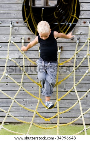 Little boy in the playground on the ropes - stock photo