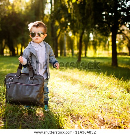 little boy in the suite with big bag in the park