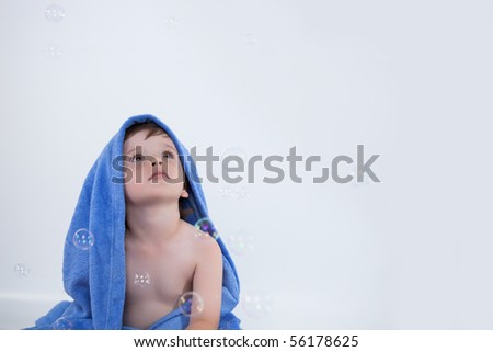 Little boy in towel looking away - stock photo