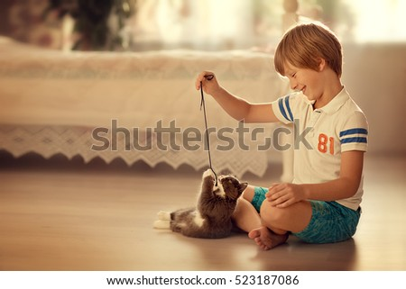 little boy in white t-shirt and shorts is playing with a kitten sitting on the floor