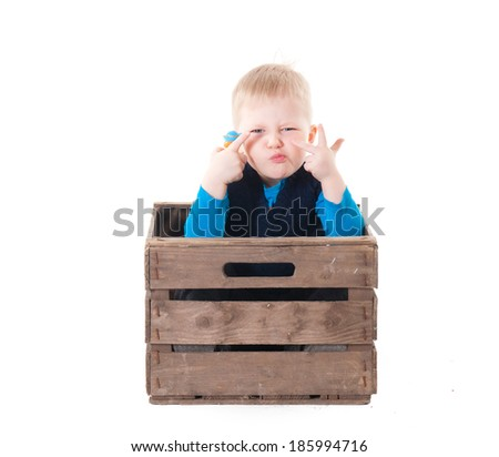 Little boy in wooden box. over white background