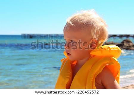 Little boy in yellow lifejacket on the seashore - stock photo