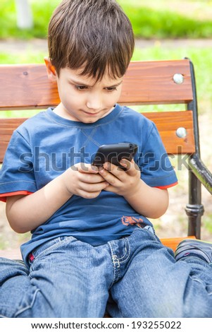 Little boy intently playing games on smartphone - stock photo