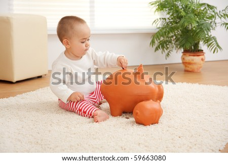 Little boy introducing a coin inside a huge piggy bank on the floor. Concept of his early savings - stock photo