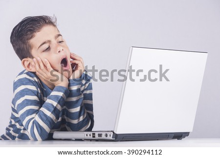 Little boy is bored while using a computer. Unhealthy lifestyle concept. Toned image with selective focus - stock photo
