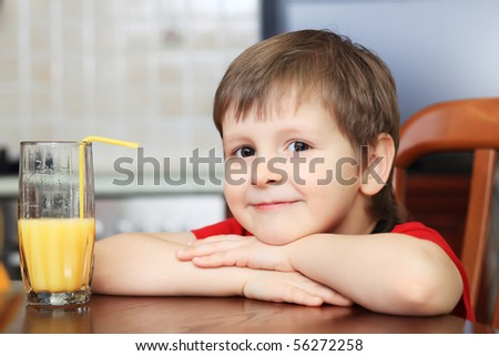 Little boy is drinking a juice at home. - stock photo