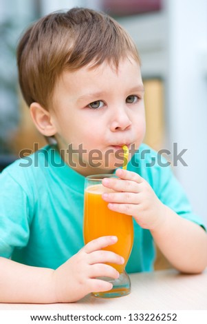 Little boy is drinking orange juice using straw - stock photo