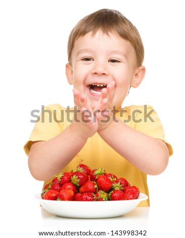 Little boy is eating strawberries and clapping his hands, isolated over white - stock photo