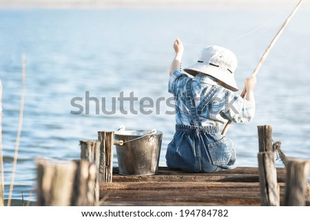 Little boy is fishing at sunset on the lake - stock photo