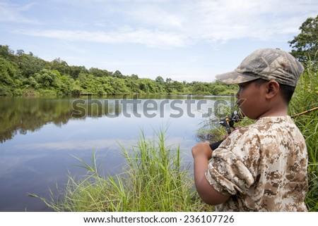 Little boy is fishing  on the lake  - stock photo