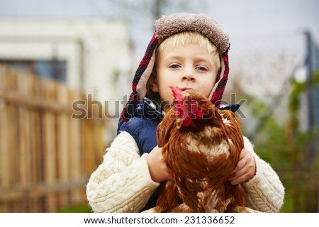 Little boy is holding the hen on the farm  - stock photo