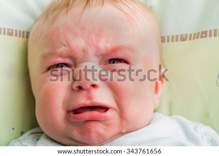 Little boy is laying down crying with big tears and drool - stock photo