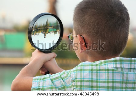 little boy is looking through magnifier in early fall park. focus on boy's ear. - stock photo