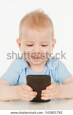 Little boy is playing with cell phone, on a gray background