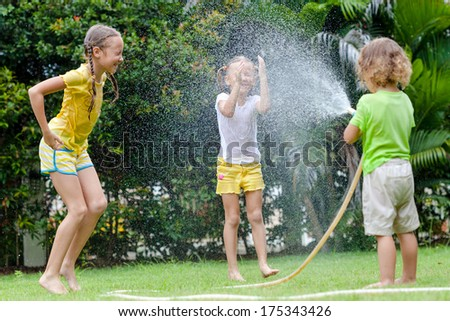 little boy is pouring a water from a hose at his sisters - stock photo