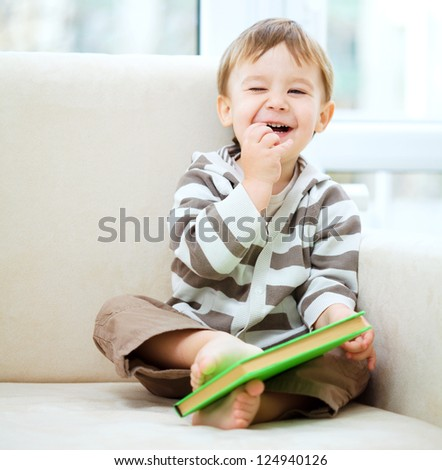 Little boy is reading book while sitting on couch, indoor shoot - stock photo