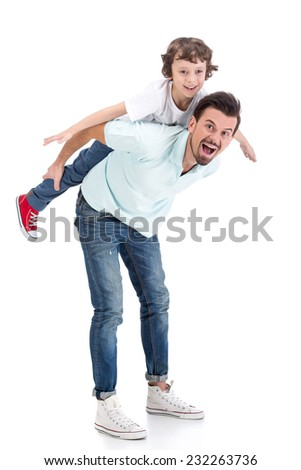 Little boy is riding dad's shoulders isolated on white background.