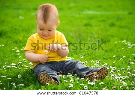 Little boy is sitting on green meadow and plays with daisy - stock photo
