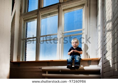 little boy is sitting on the windowsill - stock photo