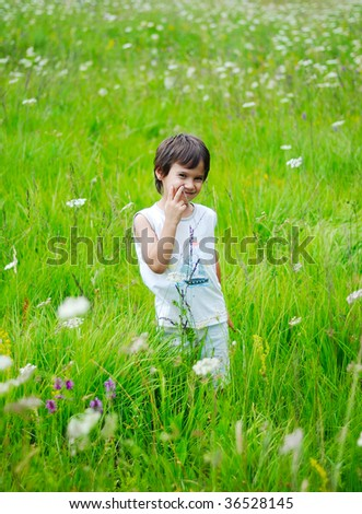 Little boy is standing on green meadow