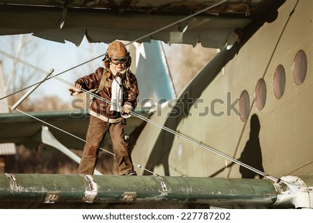 Little boy is studying airplane aviator, standing on the wing of the large aircraft - stock photo