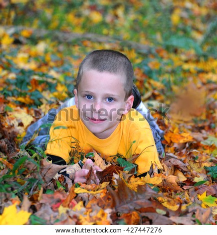 Little boy is surrounded by Fall leaves as he lays on the ground and enjoys the outdoors.  His shirt is bright yellow as are the leaves besides him.