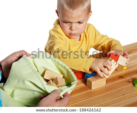 Little boy is upset while packing away wooden blocks. his father is helping him. isolated on white - stock photo