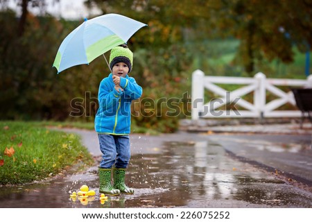 Little boy, jumping in muddy puddles in the park, rubber ducks in the puddle - stock photo