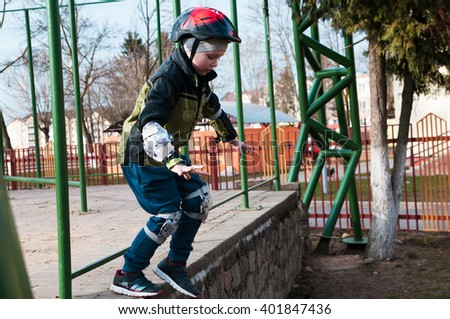 Little boy jumps on outdoors from a low altitude - stock photo