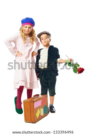 little boy keep rose in hand and little girl in green shoes posing with suitcase on white background - stock photo