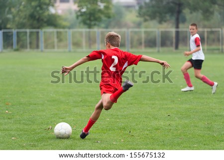 little boy kicking the ball in the game - stock photo