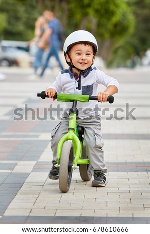 Little boy kid in helmet ride a bike in city park. Cheerful child outdoor.
