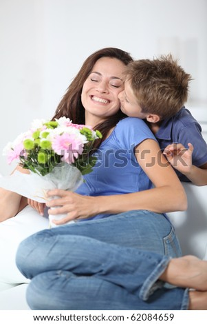 Little boy kissing his mom on mother's day - stock photo