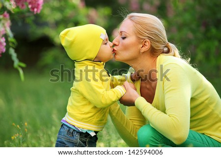 Little boy kissing his mother outdoors - stock photo