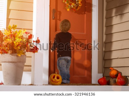 Little Boy Knocking On The Door Near Halloween Pumpkin In The Courtyard. Halloween Theme - stock photo