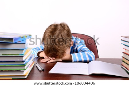 little boy laid his head on the desk on the light background, horizontal - stock photo