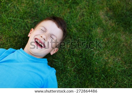 Little boy laughing in grass, outdoor portrait - stock photo
