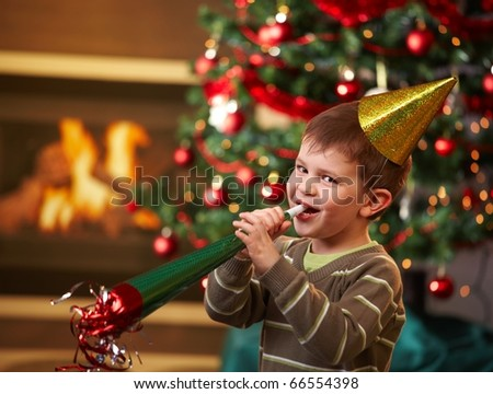 Little boy laughing on new year's eve, wearing shiny hat and blowing horn, looking at camera, christmas tree in background.? - stock photo