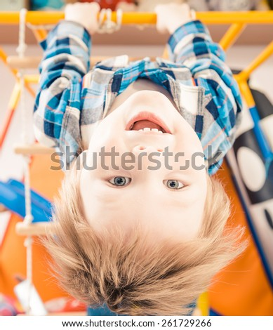 little boy laughing upside down on gym ladder - stock photo