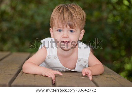 little boy laying on a picnic table looking at camera - stock photo