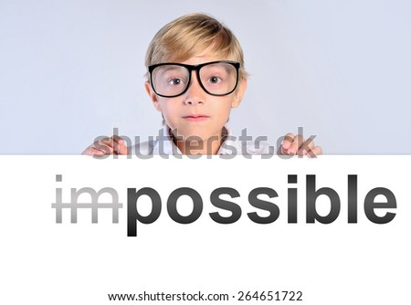 little boy leaning on paper with impossible - stock photo