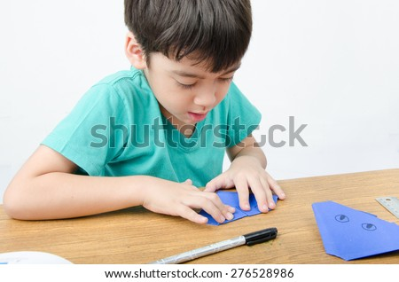 Little boy learning paper art origami - stock photo