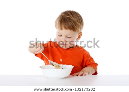 Little boy learning to feed herself - eating the oatmeal with a spoon, isolated on white - stock photo