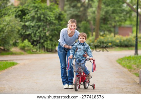Little boy learning to ride a bicycle with his mother??s help - stock photo