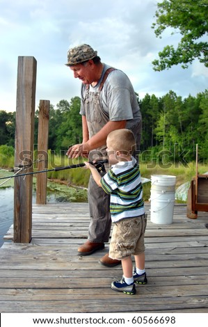 Little boy learns how to fish from his granddad.  Granddad reaches for the pole as his son catches his first bream.  Wooden dock with tree branches . - stock photo