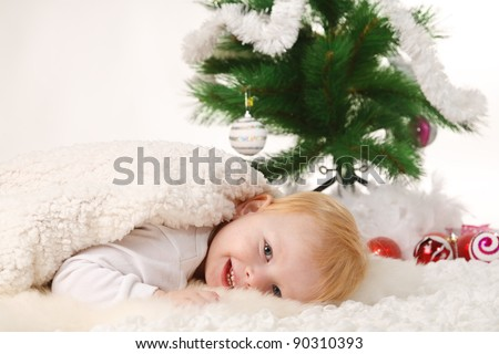 little boy lies near the Christmas tree - stock photo