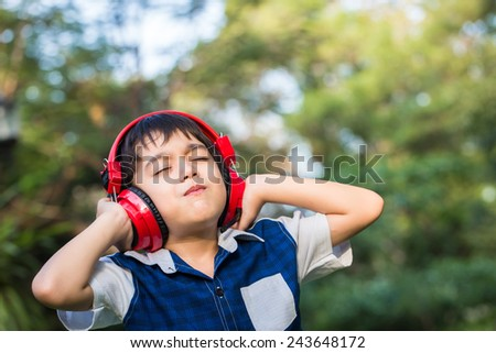 Little boy listening the music with headset in park - stock photo