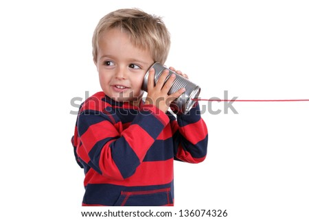 Little boy listening through a tin can phone connected by string, concept for communication - stock photo