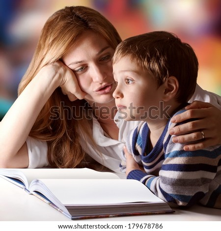 Little boy listening to his mother telling him stories - stock photo